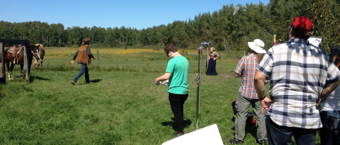 On set of the Barbara Blackwood Movie: crew in foreground, a horse and 2 actors in background. Green pasture/farm with trees in distance and blue sky above.